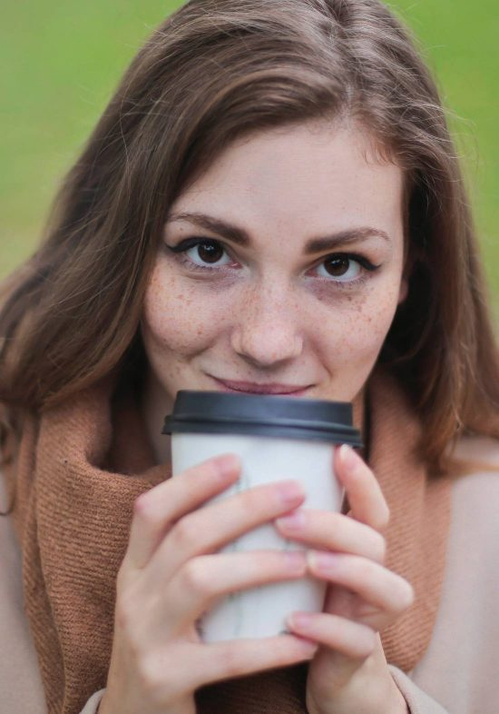 Patron enjoying a cup of hot coffee with both hands while smiling at camera.