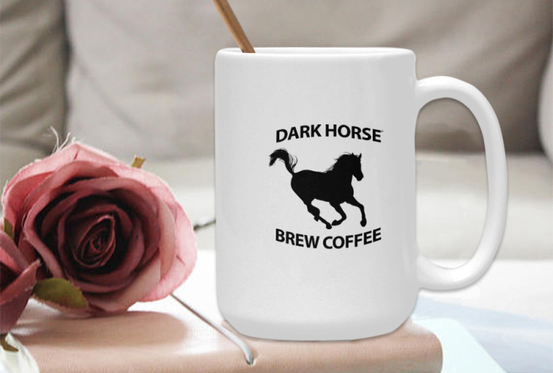 Dark Horse Brew Coffee branded coffee mug sitting on a stack of books with a flower laying to the side.